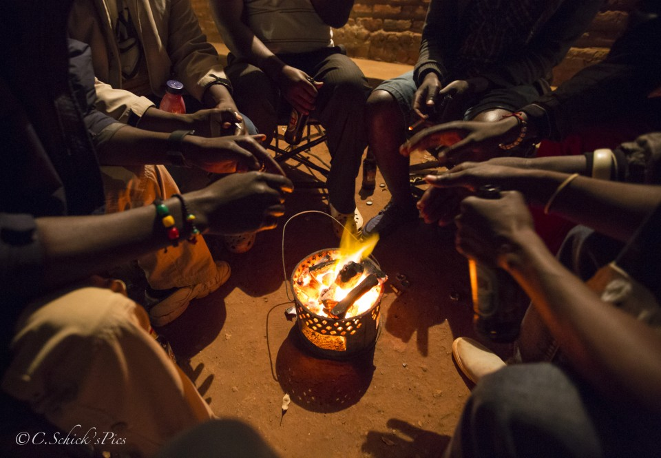 A group of me sit around a coal fire to keep warm outside the bar of Doris Ngwenya, a hip, independent, successful business owner,at Mwali border in Zambia, on June 7, 2016. -- (Crystal Schick/Independent Photojournalist)