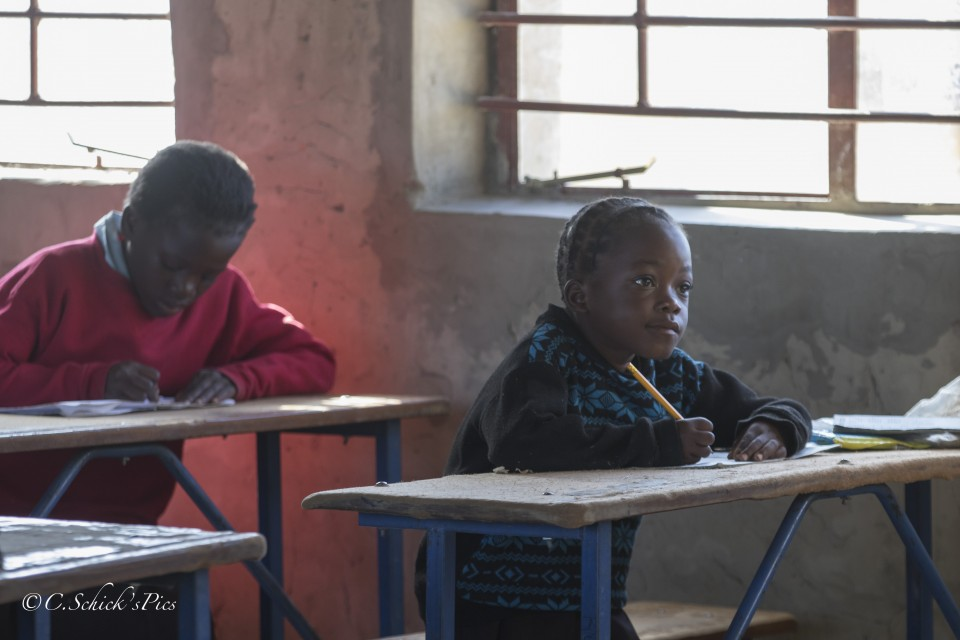 One of Fizwell's students watches attentively as he writes questions on the chalkboard in a rural school about 30 minutes outside Chibombo in Zambia, on June 9, 2016. -- (Crystal Schick/Independent Photojournalist)