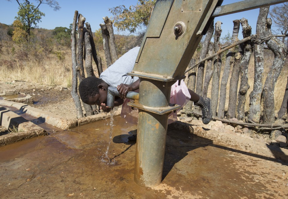 Siphiwe shows me how she drinks what from a hand pump bore hole built by World Vision with funds from western sponsors at Mutala Basic School in Kalomo district in Zambia, on June 16, 2016. -- (Crystal Schick/Independent Photojournalist)